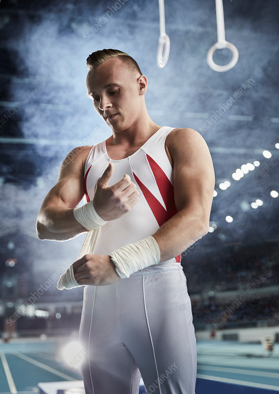 Male gymnast wrapping wrists