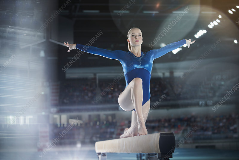 Female gymnast performing on balance beam