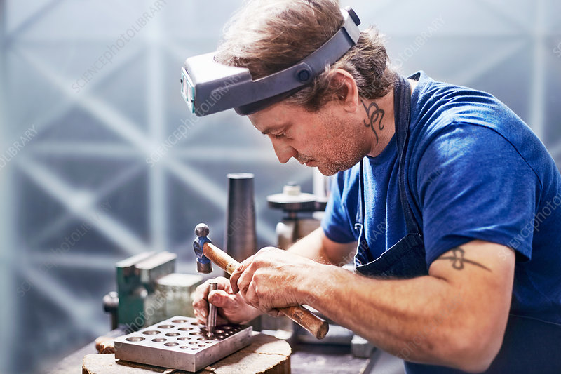 Focused jeweller using hammer in workshop