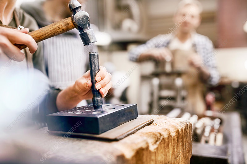 Jeweller using hammer and equipment in workshop