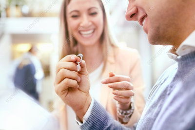Jeweller helping man shopping for diamond ring