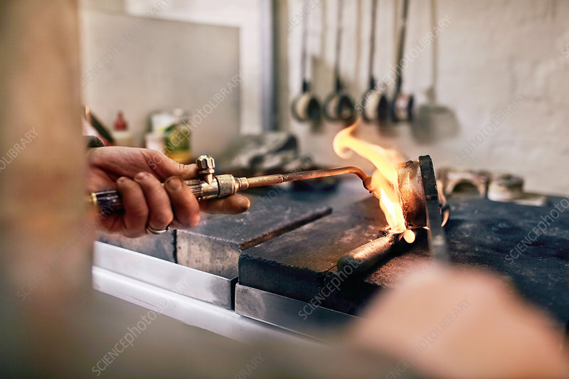 Jeweller heating metal with torch in workshop