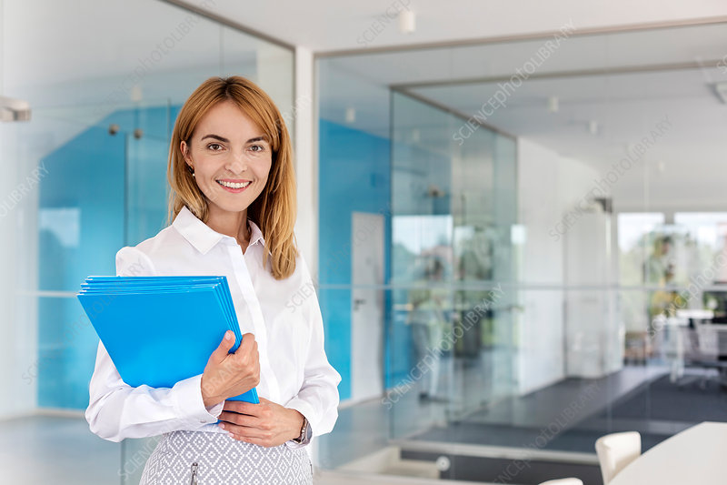 Portrait smiling businesswoman holding folders