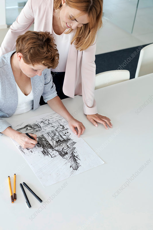 Female designers drawing sketch in conference room