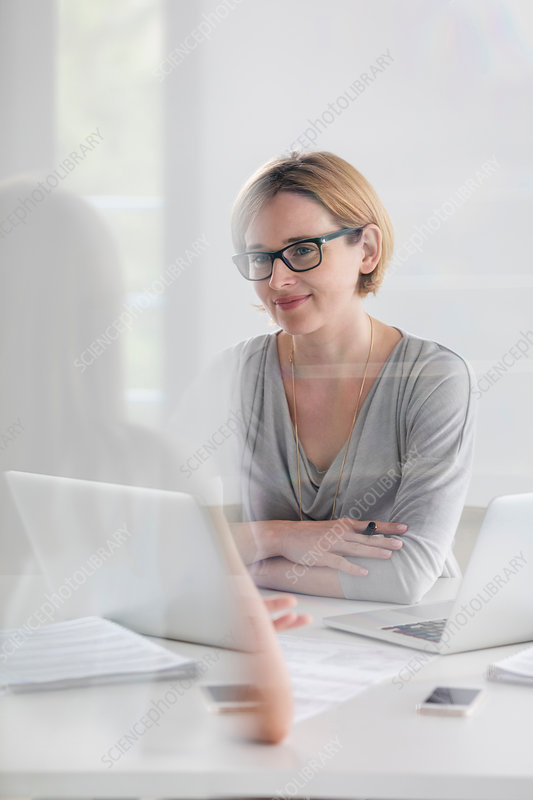 Portrait confident businesswoman working at laptop