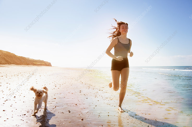Young woman and dog running on sunny beach