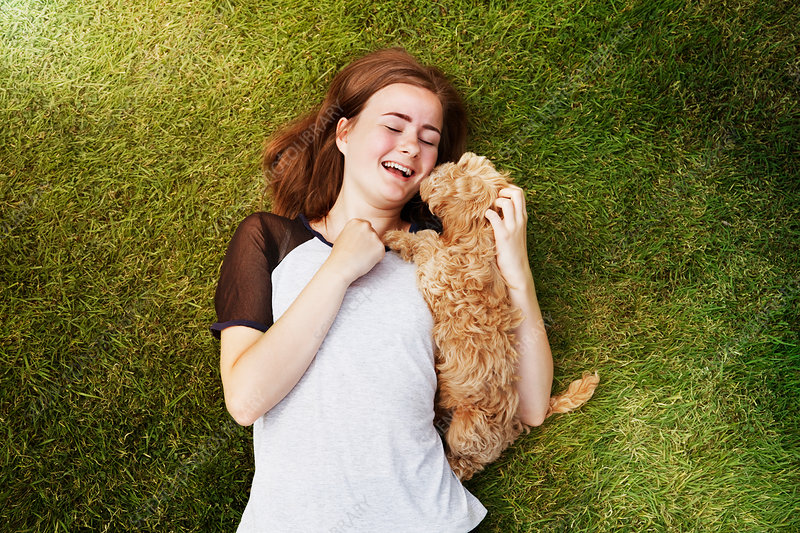 Young woman cuddling affectionate dog in grass
