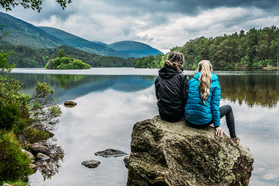 Couple sitting on rock, Loch an Eilein, Scotland