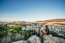 Couple sitting on rocks, Athens, Greece