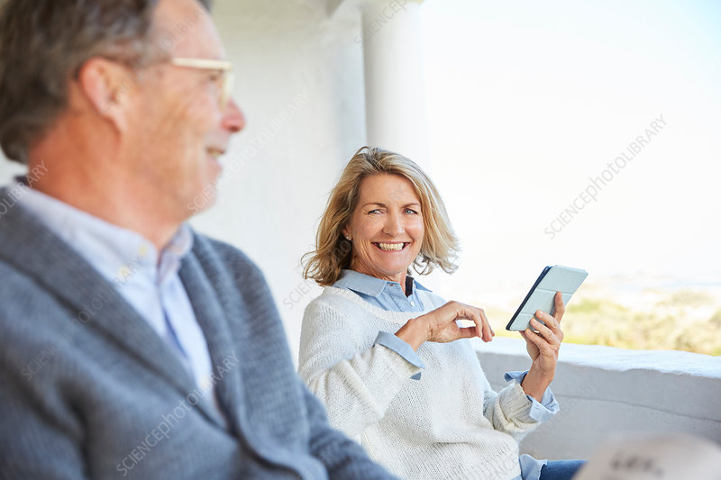 Senior couple using digital tablet on patio