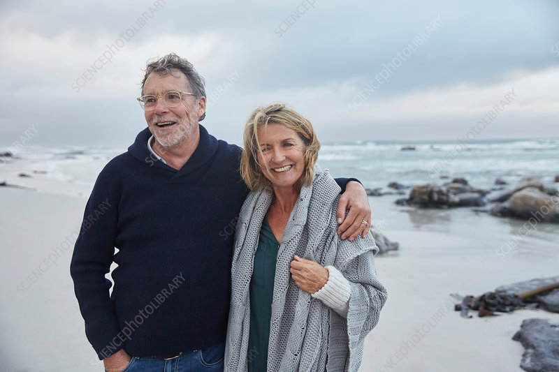 Smiling senior couple hugging on stormy beach