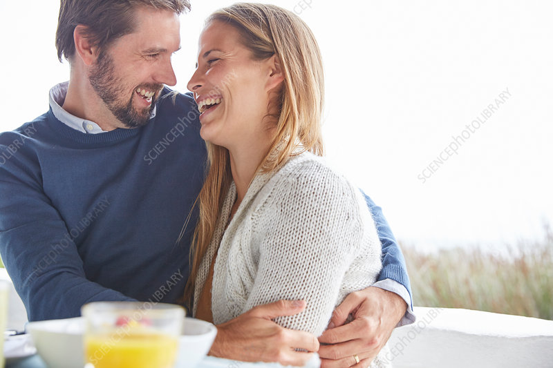 Happy couple hugging and laughing on patio