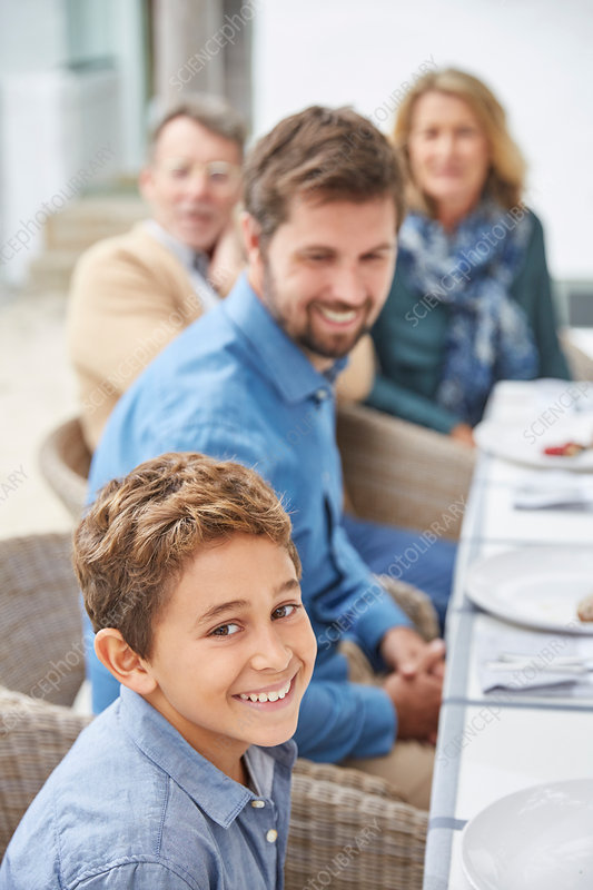 Portrait smiling boy enjoying lunch with family