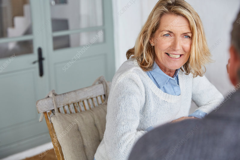 Smiling senior woman talking to husband on patio
