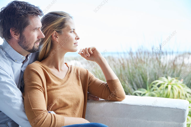 Serene couple looking away on patio