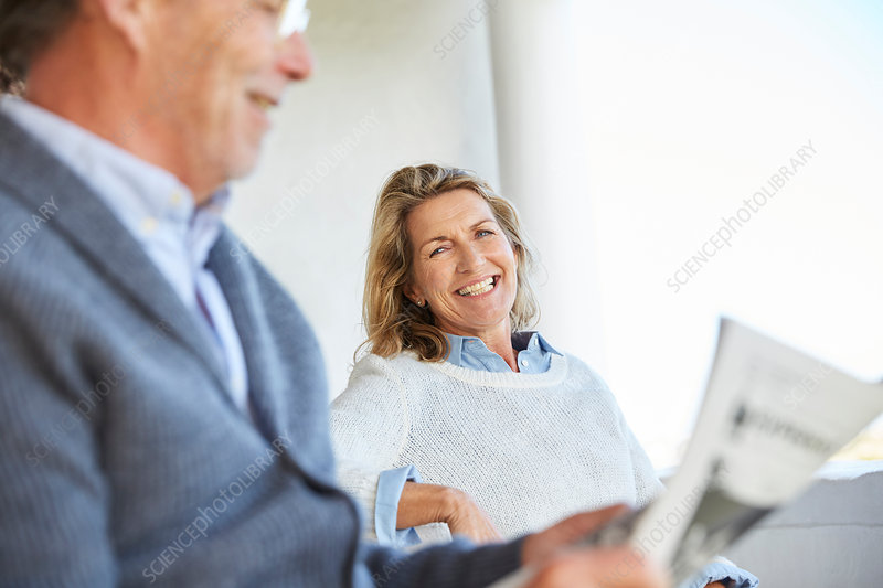 Smiling senior couple reading newspaper on patio