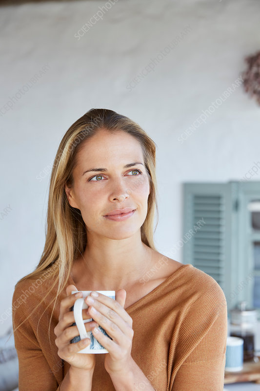 Serene woman drinking coffee and looking away
