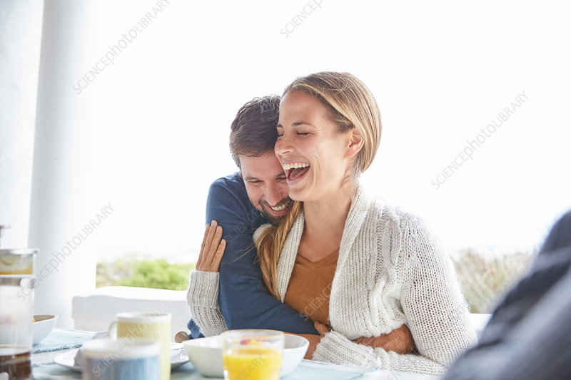 Couple hugging and laughing at breakfast