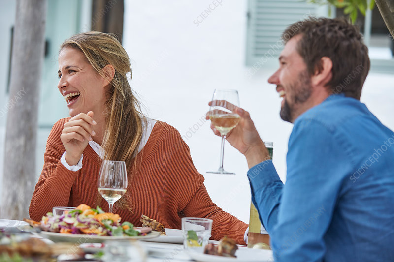 Couple drinking wine and eating at patio table
