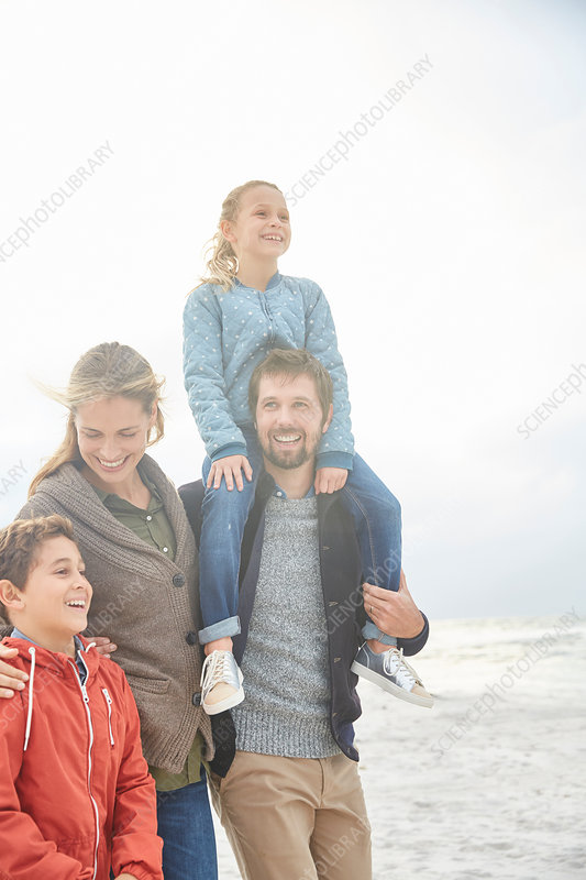 Smiling family walking on winter beach