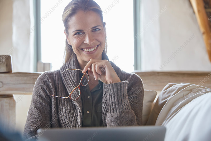 Portrait smiling woman using laptop on sofa