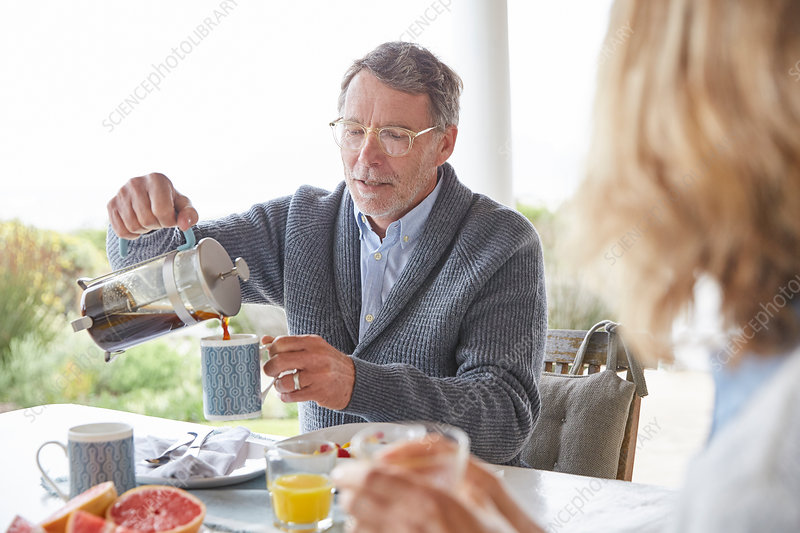Senior man pouring coffee from French Press