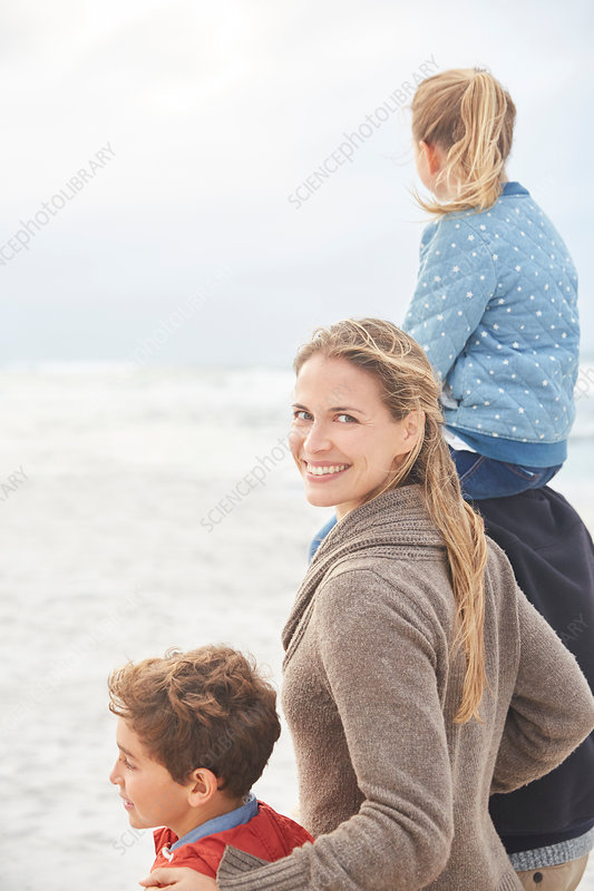 Portrait smiling family walking on winter beach