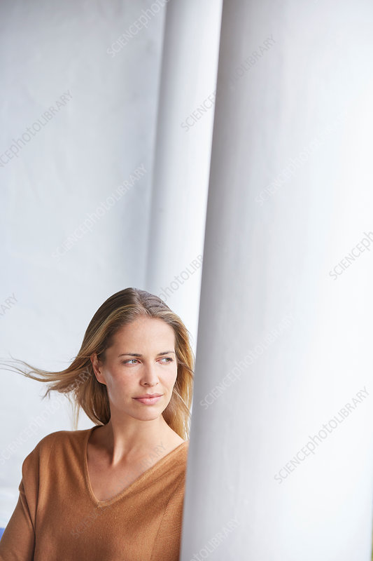 Pensive blonde woman looking away on patio