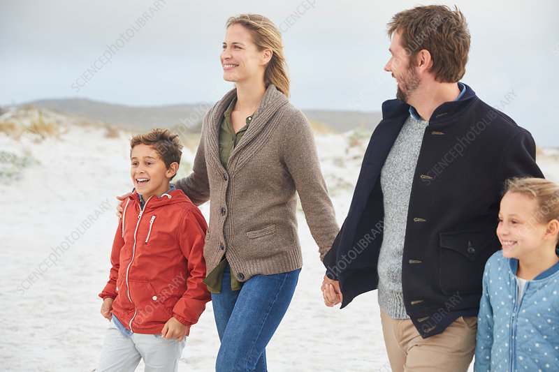 Family holding hands walking on winter beach