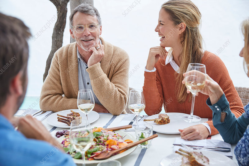 Couples drinking wine and eating at patio table
