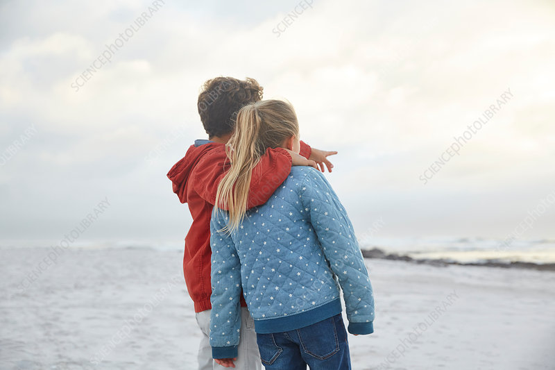 Brother and sister looking at winter ocean