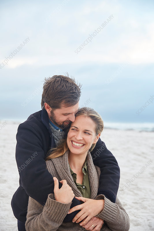 Smiling couple hugging on winter beach