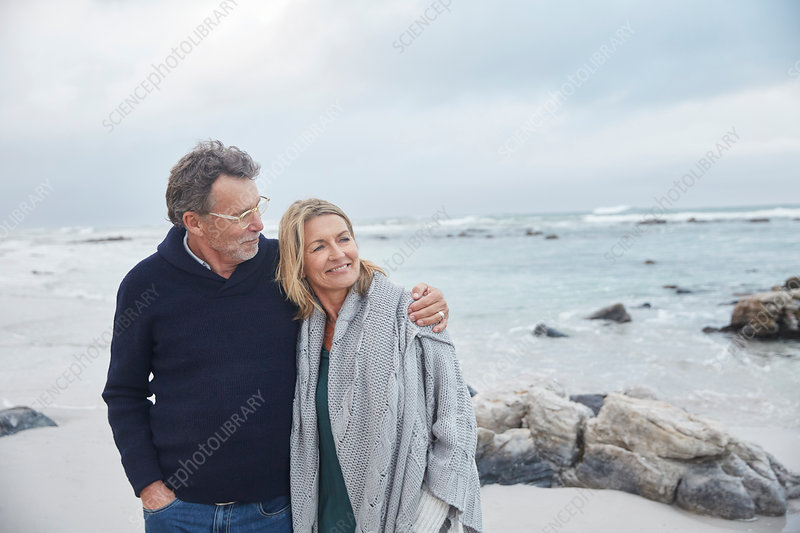 Affectionate couple hugging on winter beach