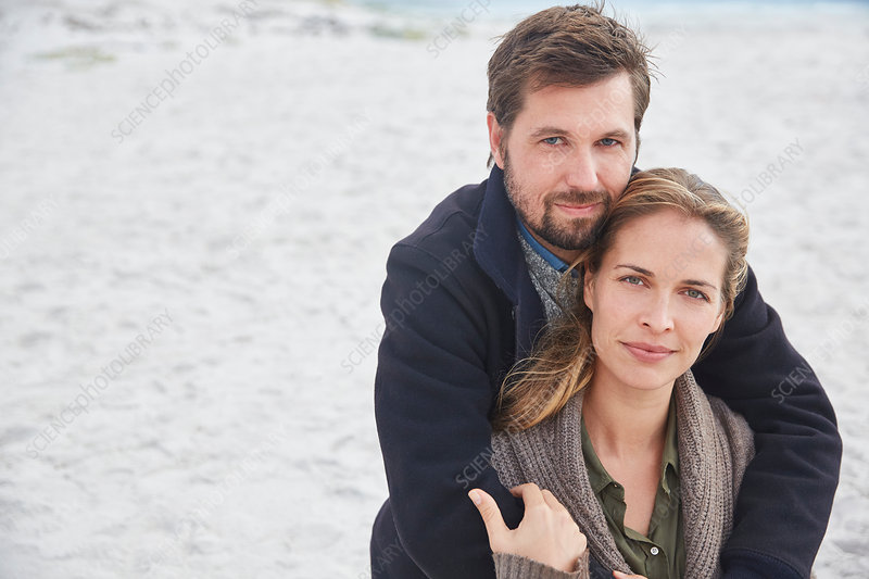Portrait serene couple hugging on beach
