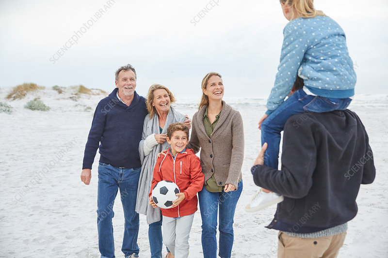 Family with soccer ball on winter beach