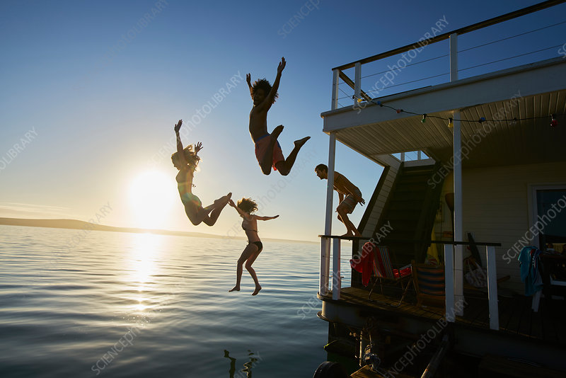 Friends jumping off summer houseboat