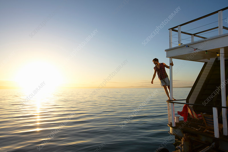 Man leaning on summer houseboat railing