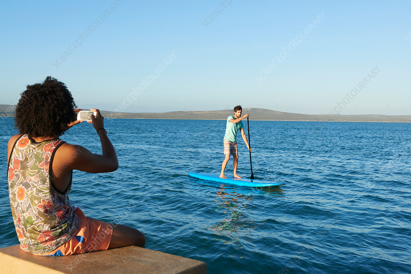 Young man photographing friend paddleboarding