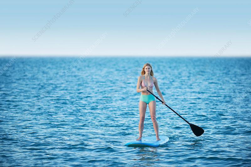 Young woman in bikini paddleboarding
