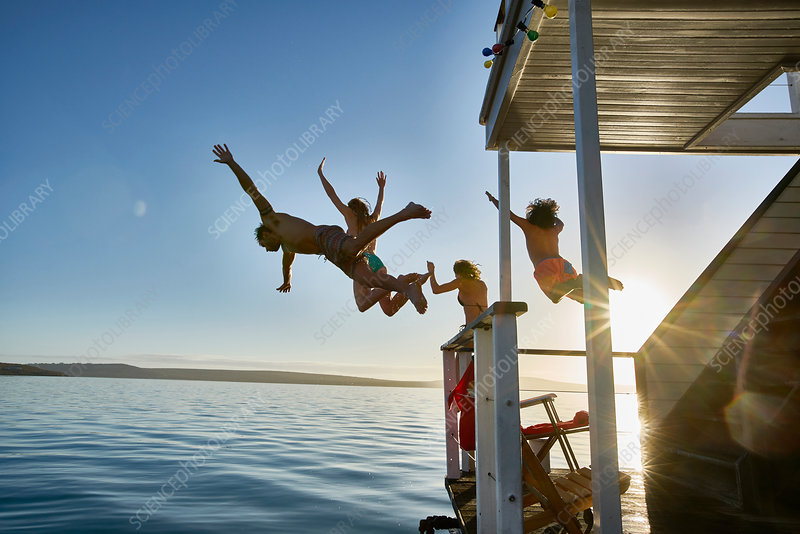 Friends jumping from summer houseboat