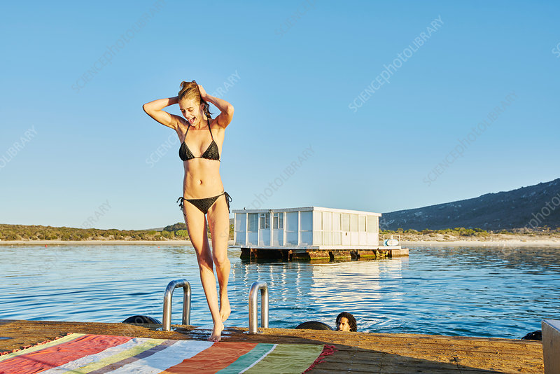 Young woman in bathing suit on sunny summer dock