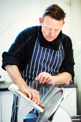 Butcher in apron slicing salami with a slicer