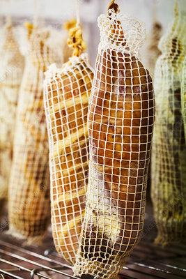 Air dried meat wrapped in nets, hanging