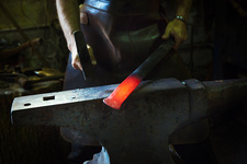 A blacksmith strikes a length of red hot metal with a hammer