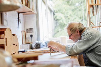 A violin maker at his drawing board drawing out the plans