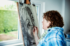 An artist working at her easel using charcoal on paper