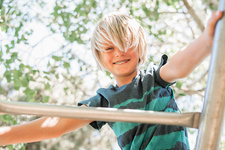 Blond boy on a climbing frame in a garden