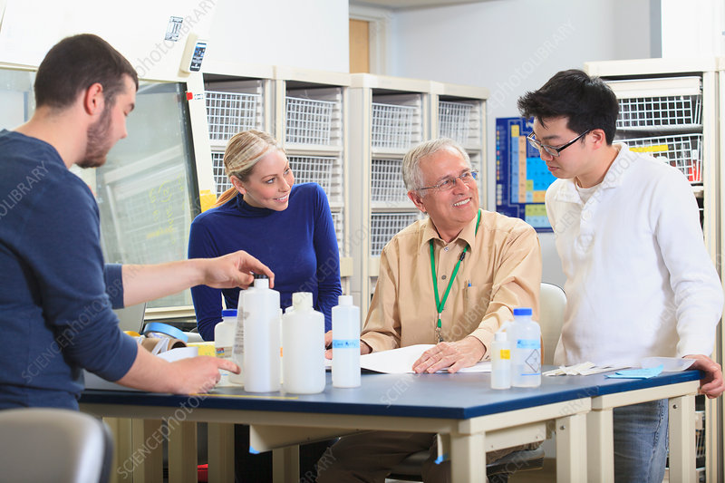 Professor with students in chemical laboratory