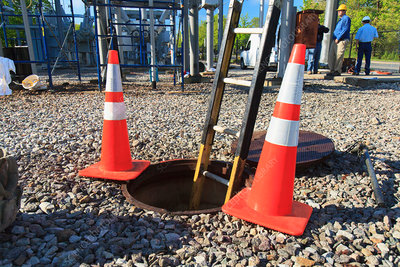 Ladder in manhole and warning cones