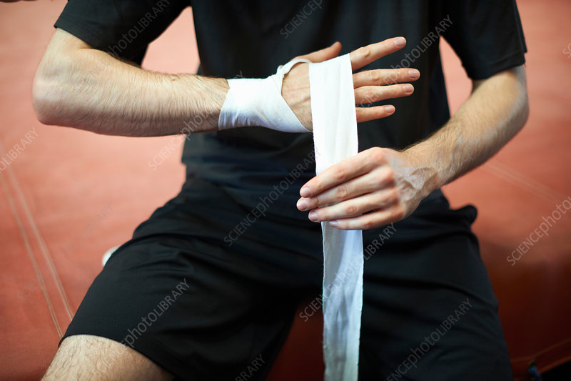 Boxer bandaging hands before putting on gloves
